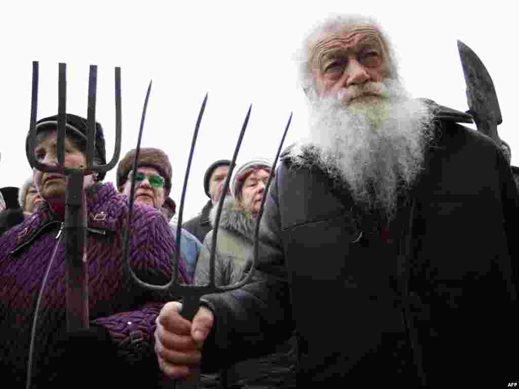 Protesters hold pitchforks and spades during a rally in front of the city administration building in Donetsk, Ukraine, on November 28 in support of demands by World War II and Afghan war survivors as well as Chornobyl cleanup crews. (AFP Photo/Alexander K
