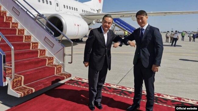 Министр иностранных дел Кыргызстана Чингиз Айдарбеков (справа) встречает в аэропорту главу внешнеполитического ведомства Китая Вана И. 13 сентября 2020 года.