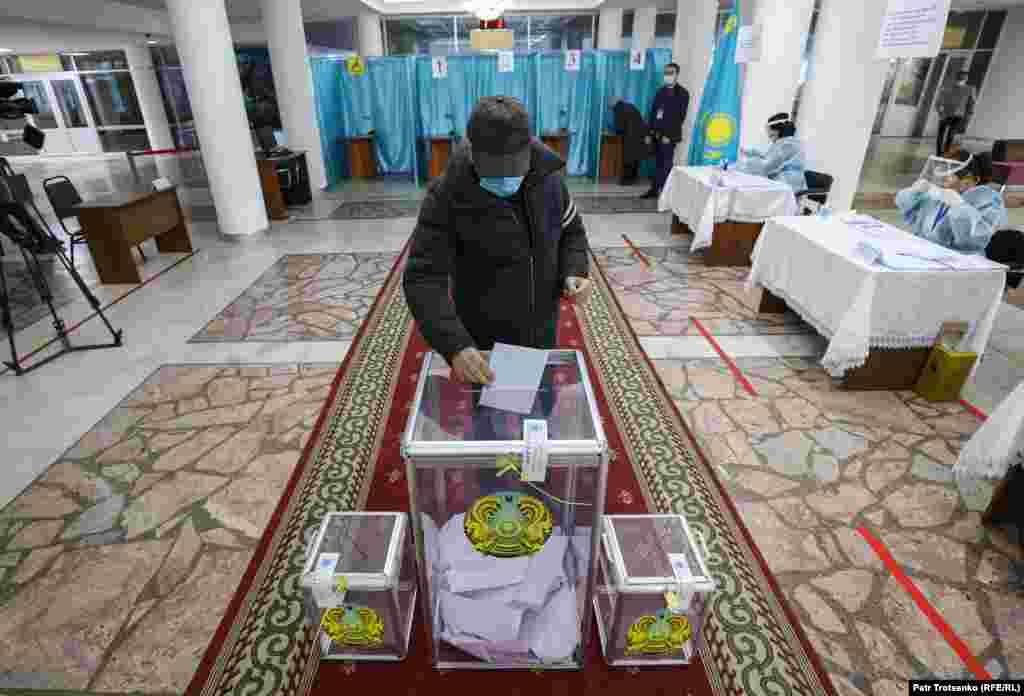 A voter wearing a protective mask votes during parliamentary and local elections in Kazakhstan's largest city, Almaty, on January 10.