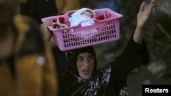 نازحة من الرمادي تحمل طفلها