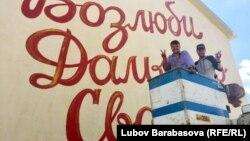 Художники разукрашивают фасад дома в микрорайоне Дальнее