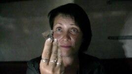 Світлана, яка втекла з зони конфлікту, показує осколок снаряда, який влучив у її будинок