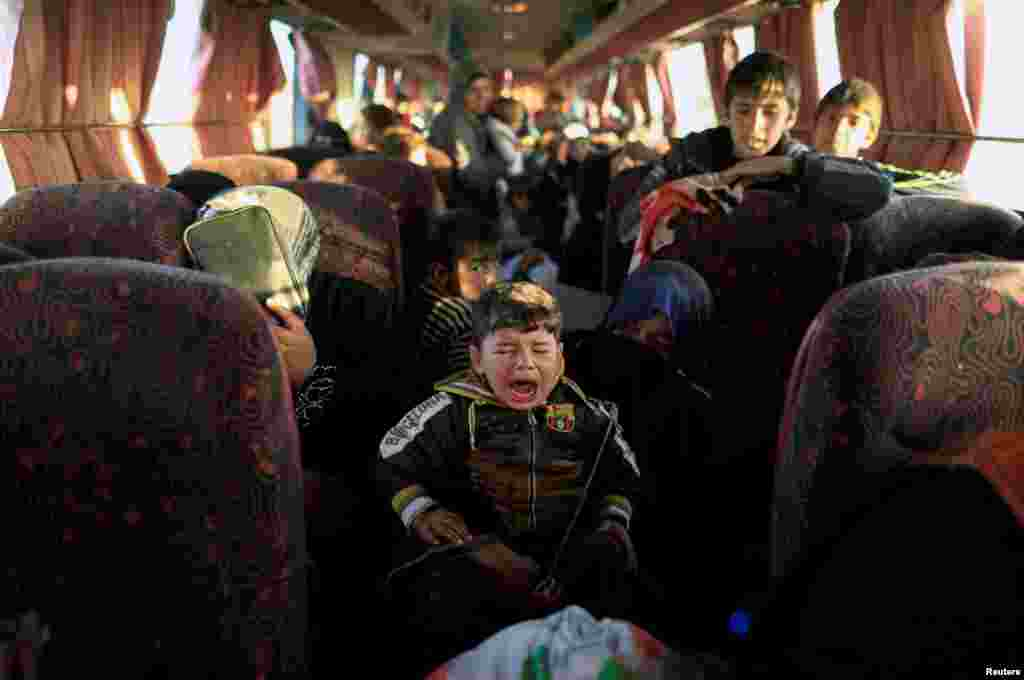 An Iraqi boy who just fled a village controlled by Islamic State fighters cries as he sits with his family inside a bus before heading to a camp for the displaced near Mosul. (Reuters/Zohra Bensemra)