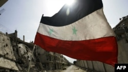 Սիրիայի պետական դրոշը Հոմս քաղաքի Բաբա Ամր արվարձանում` ռազմական շինությունների կողքին