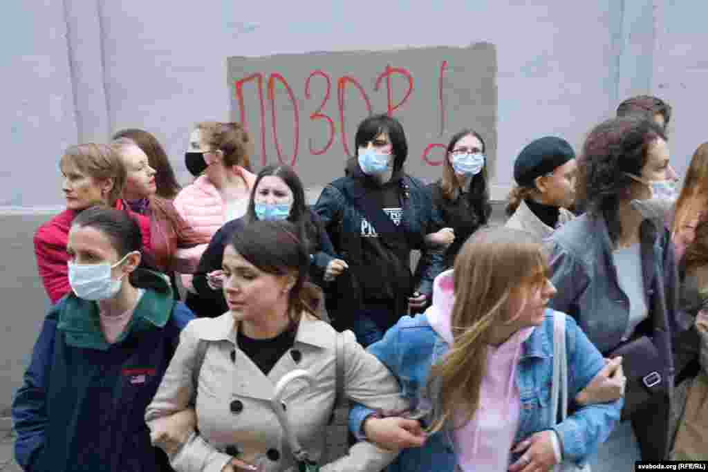 """Protesters link arms in front of a wall where the word """"SHAME!"""" has been written."""