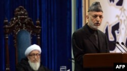 Afghan President Hamid Karzai (right) addresses the Loya Jirga on its opening day on November 21 as the council's head, Sibghatullah Mojaddedi, listens.