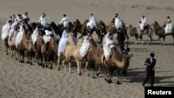 Церемония массовой свадьбы в округе Юли Синьцзян-Уйгурского автономного региона Китая. Женихи ведут верблюдов, на которых сидят их невесты. Иллюстративное фото. 2 ноября 2014 года.