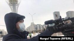 Сотрудник сил безопасности закрывает рукой объектив камеры Азаттыка. Нур-Султан, 11 декабря 2020 года.
