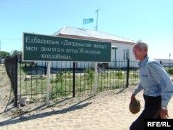 Ауылдық әкімдік кеңсесі алдынан өтіп бара жатқан адам. Мақат ауданы, Атырау облысы, шілде, 2009 жыл. Көрнекі сурет.