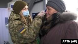 Українська військова перевіряє температуру літньої жінки на пункті пропуску в Майорську Донецької області