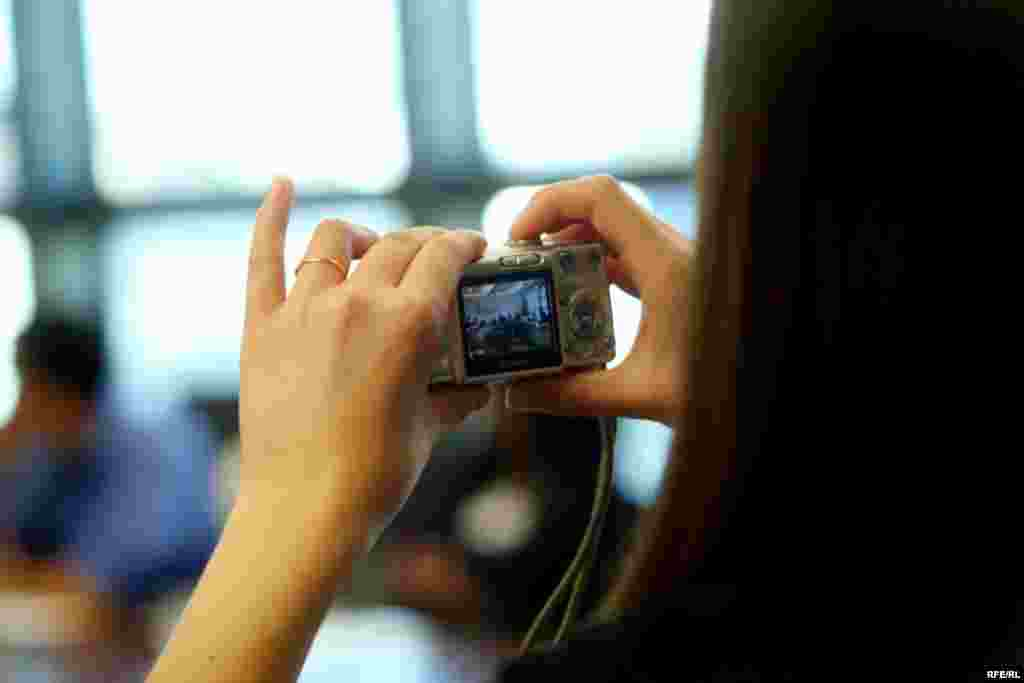 A student takes a photo in the conference room where RFE/RL's daily editorial meetings are held.