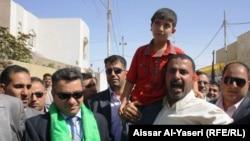الطفل المختطف بعد تحريره بين والده ومحافظ النجف