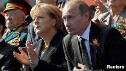 Ангела Меркель Владимир Путин белән бергә Җиңүнең 65 еллыгы парадын карый. Меркель 70 еллык парадында булмаячак