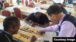 Абубакир Ибрахим из Ганы (в центре) обсуждает результаты игры в тогызкумалак. Алматы, 16 апреля 2015 года.