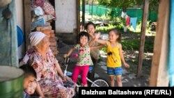 Пожилая женщина рядом с детьми во дворе частного дома в Алматы. Июнь 2016 года.