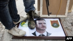 Syria -- Rebels stand on a picture of President Bashar al-Assad in the northern city of Aleppo, 20Aug2012