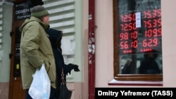 People look at an electronic board displaying currency exchange rates in Vladivostok on March 10.