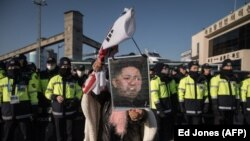 Південний кореєць тримає перекреслений портрет північнокорейського лідера Кім Чен Ина, протестуючи проти прибуття порому з північнокорейським оркестром у порту Мукхо в місті Тонхе. 6 лютого 2018 року