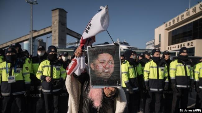 Південний кореєць тримає портрет північнокорейського лідера Кім Чен Ина, протестуючи проти прибуття парому з північнокорейським оркестром у порту Мухо в Донгае. 6 лютого 2018 року