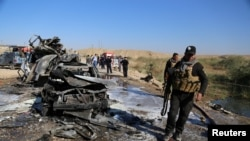 Iraqi security forces inspect the site of a deadly bomb attack in Tikrit on November 6.