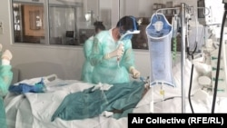 Доктор у постели пациента, больного коронавирусом.