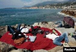 Африканські мігранти, що хочуть потрапити з Італії у Францію, сплять на березі, червень 2015 року