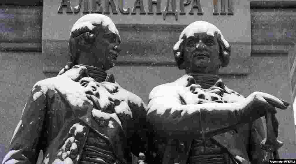Засніжені скульптури князів Григорія Потьомкіна і Василя Долгорукого біля основи пам'ятника російській цариці Катерині II