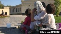 Женщина с детьми просит милостыню перед мечетью. Шымкент, 9 октября 2019 года.