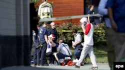 A person is treated by emergency workers as members of the Republican congressional baseball team look on following a shooting in Alexandria, Virginia, on June 14.