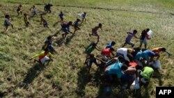 Жителі одного з сіл на Філіппінах біжать за гуманітарною допомогою, яку на них скинули з літака