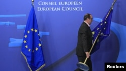 An employee at the EU council in Brussels on November 22 adjusts European Union flags at the entrance of the council headquarters for an EU leaders' summit discussing the bloc's long-term budget.