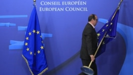 Belgium -- An employee at the EU council adjusts European Union flags at the entrance of the council headquarters for an European Union leaders summit discussing the European Union's long-term budget in Brussels, 22Nov2012