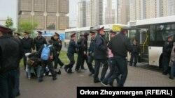 Полицейские ведут задержанных активистов движения «ипотечников» к автобусам. Астана, 22 мая 2013 года.