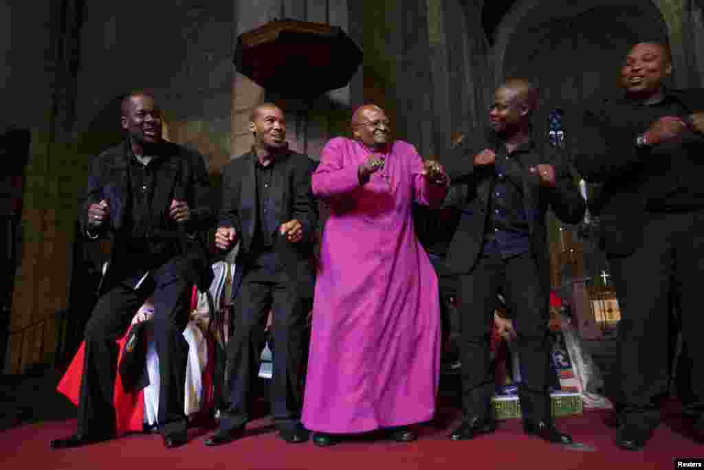 South African Archbishop Emeritus Desmond Tutu (center) dances with the Cape Town Opera Ensemble at the Templeton Prize celebration at St. George's Cathedral in Cape Town. Tutu won the 2013 Templeton Prize, worth $1.7 million, for helping inspire people around the world by promoting forgiveness and justice. (Reuters/Ilan Godfrey)