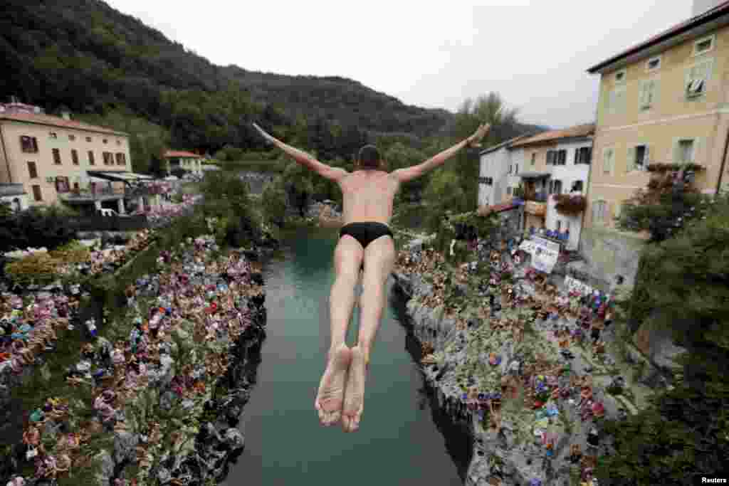 A competitor jumps from the old bridge during a cliff-diving competition in Kanal ob Soci in southwestern Slovenia. (Reuters/Srdjan Zivulovic)