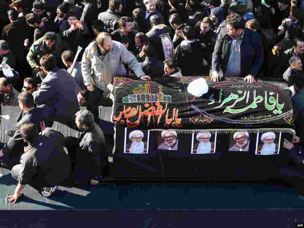 The coffin of Montazeri, who was one of the highest Shi'ite authorities, passes through mourners.