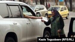 Қайыр сұраған әйелге көлікте отырған адам садақа беріп жатыр. Алматы, 31 наурыз 2012 жыл.