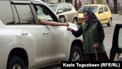 Женщина просит милостыню на одном из перекрестков Алматы.