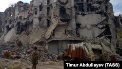 Алеппо қаласында соғыстан қираған ғимараттың жанында тұрған адам. Сирия, 14 желтоқсан 2016 жыл.