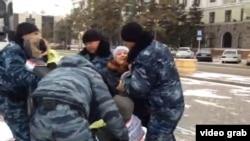 Полицейские задерживают участников акции протеста, требующих предоставления альтернативного жилья вместо сносимого. Астана, 11 ноября 2014 года.
