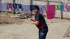 O femeie romă pune hăinuțe la uscat, satul  Schinoasa, Călărași.