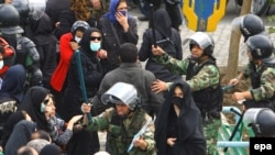 Riot police clash with opposition protesters in Tehran on November 4.