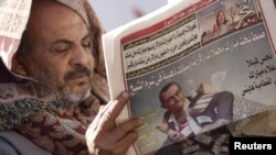 A man reads a local newspaper on Tahrir Square in Cairo.