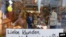 """""""Dragi clienți, putem deschide din nou"""" scrie în vitrina unui magazin de ciocolată și vinuri din Ludwigsburg, Germania, 20 aprilie 2020."""