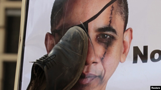 A protester hits a portrait of U.S. President Barack Obama with a shoe -- a gesture of insult in the Arab world -- in front of the U.S. Embassy in Cairo last spring.