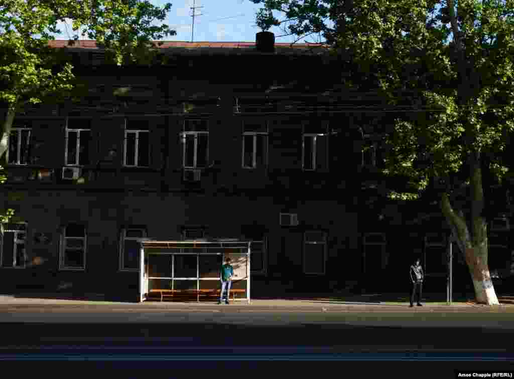 Two men wait for a bus in the morning light in central Yerevan.After weeks of protest that included nonviolent acts of dissent, there was almost no sign of the political crisis gripping Armenia.