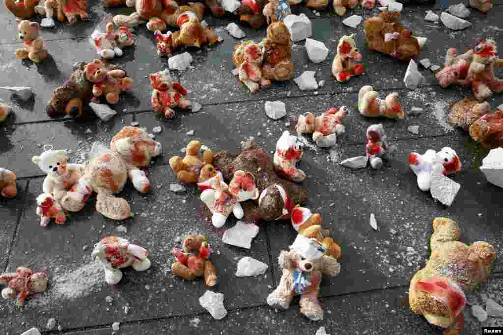 Teddy bears with bandages are left on the ground by protesters during a demonstration in front of the German Chancellery prior to a visit by Russian President Vladimir Putin in Berlin on October 19. (Reuters/Axel Schmidt)