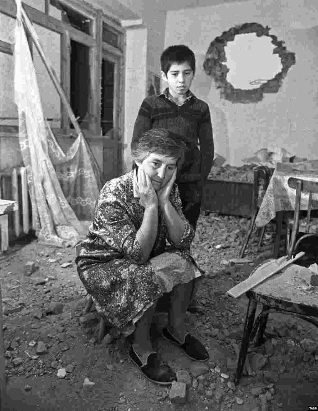 """Egy súlyosan megrongált otthon és lakói az 1991-es orosz-grúz konfliktus kirobbanásakor. A Szovjetunió összeomlásakor kirobbanó összecsapásokat a """"legértelmetlenebb"""" háborúnak titulálták, amelynek hatásai a mai napig érzékelhetőek a térségben."""