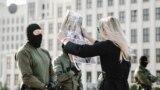 Удзельніца жаночага маршу паказвае сілавіку ў ачапленьні Дому ўраду фота з параненымі падчас пратэстаў людзьмі, Менск, 5 верасьня 2020 г.