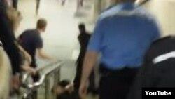 Скриншот появившегося в Интернете видео, в котором милиционеры тащат вниз по лестнице инвалида.